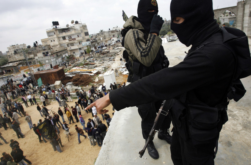 KHAN YOUNIS, GAZA STRIP - MARCH 27: Islamic Jihad militants watch over a crowd from atop a mosque during the funeral of Haithem Arafat, 23, who was killed on Friday in clashes with Israeli soldiers, on March 27, 2010, Khan Younis, Gaza Strip. Two Israeli soldiers and at least one Palestinian militant were killed Friday, during clashes on the Israel/Gaza border. (Photo by Warrick Page/Getty Images)
