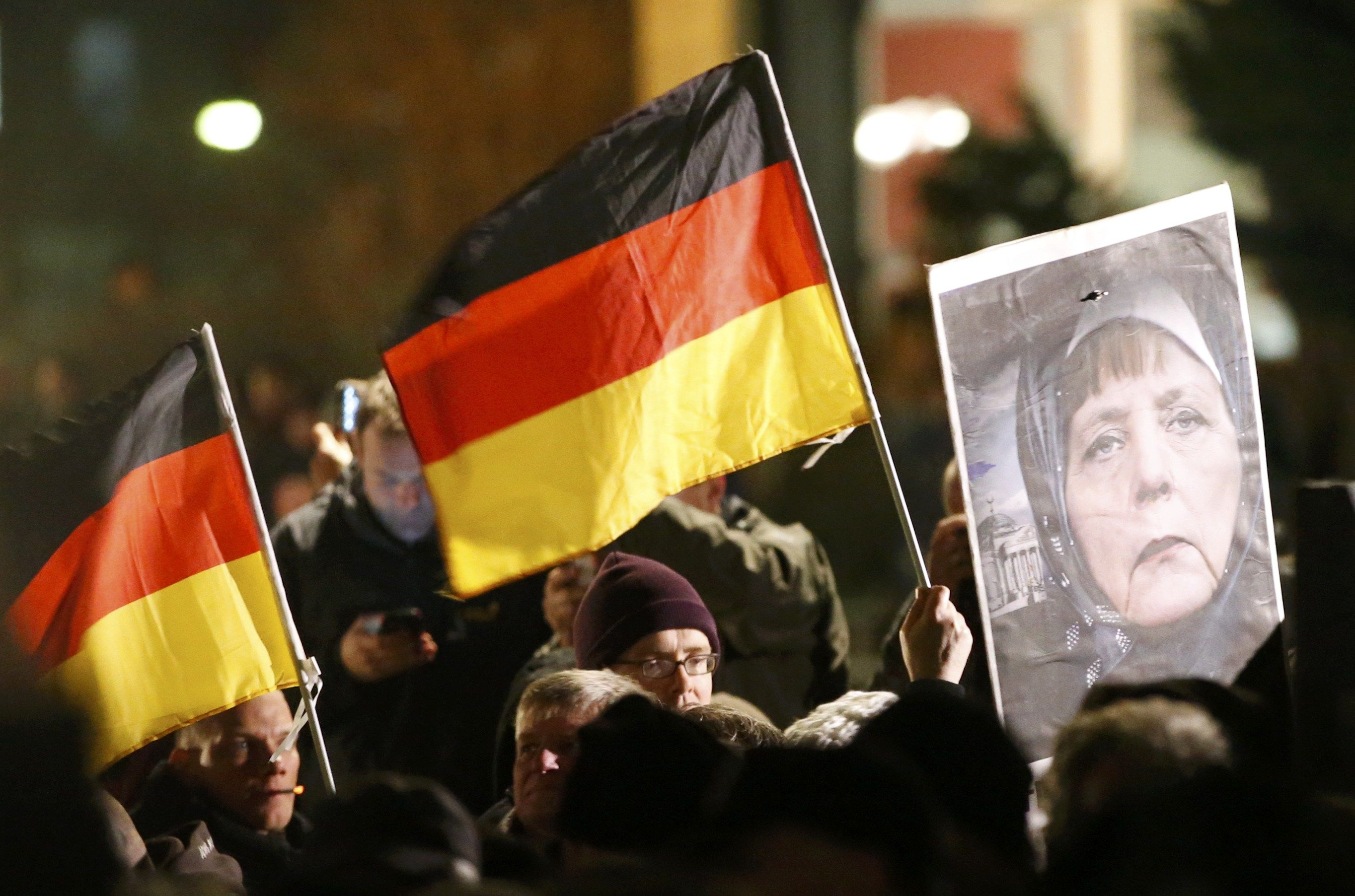 Supporters of anti-immigration movement Patriotic Europeans Against the Islamisation of the West (PEGIDA) hold German flags and a portrait depicting German Chancellor Angela Merkel during a demonstration in Dresden January 12, 2015.       REUTERS/Fabrizio Bensch (GERMANY  - Tags: POLITICS CIVIL UNREST)