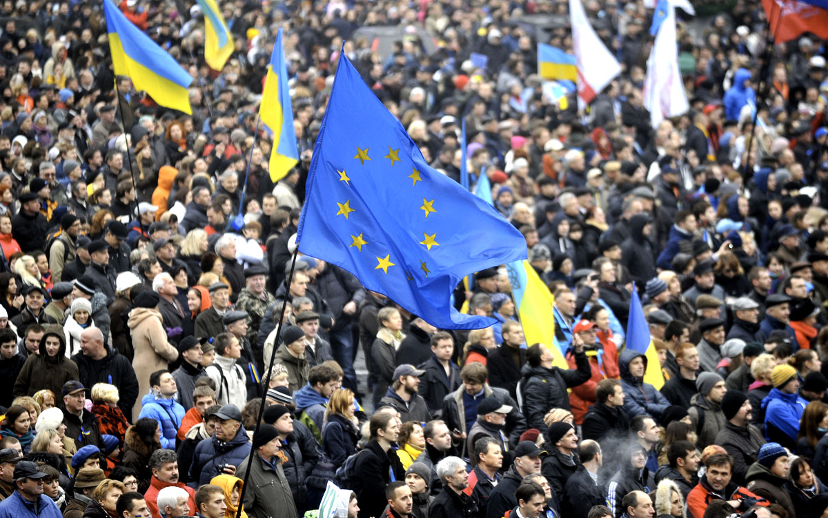 People wave a EU flag and Ukrainian national flags during a rally in Kiev on November 24, 2013. Pro-West Ukrainians on Sunday staged the biggest protest rally in Kiev since the 2004 Orange Revolution, demanding that the government sign a key pact with the European Union and clashing with police. The opposition called the rally after President Viktor Yanukovych's government reversed a plan to sign a historic deal deepening ties with the European Union, in a U-turn critics said was forced by the Kremlin. AFP PHOTO/GENYA SAVILOV        (Photo credit should read GENYA SAVILOV/AFP/Getty Images)