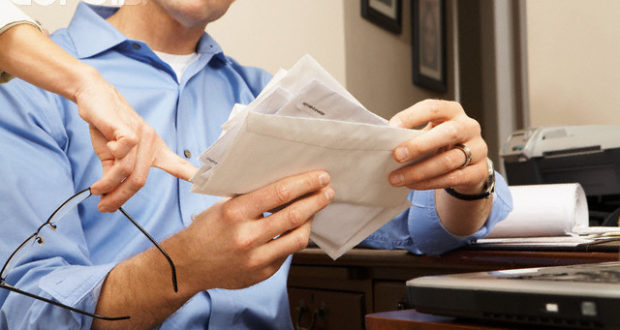 Couple Going Through Mail and Paying Bills --- Image by © Jack Hollingsworth/Corbis